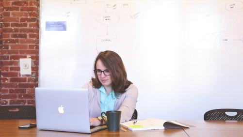 Eine Lehererin die eine Virtuelle Schulstunde an ihrem Notebook vorbereitet